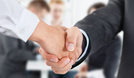 Male and female handshake in office. Businessman in suit shaking woman's hand. Serious business and partnership concept. Partners made deal, sealed with Stock Photography