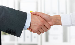 Male and female handshake in office. Businessman in suit shaking woman's hand. Serious business and partnership concept. Partners made deal, sealed with Royalty Free Stock Photos