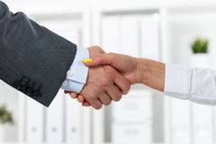 Male and female handshake in office. Businessman in suit shaking woman's hand. Serious business and partnership concept. Partners made deal, sealed with Royalty Free Stock Images