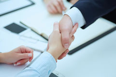 Male and female handshake in office. Businessman in suit shaking woman`s hand. Serious business and partnership concept. Partners made deal and sealed it with Stock Image