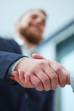 Male and female handshake in office. Businessman in suit shaking woman`s hand. Serious business and partnership concept. Partners made deal, sealed with Royalty Free Stock Images