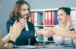 Male and female handshake in office. Serious business and partnership concept. Partners made deal, sealed with handclasp. Male and female handshake in office Royalty Free Stock Photos