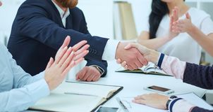 Male and female handshake in office. Businessman in suit shaking woman`s hand in the meeting room. Male and female handshake in office. Serious business and Stock Photos