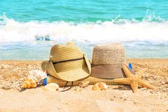 Male and female hats on the beach Stock Photo