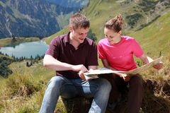 Male and female hikers in the Alps. Male and female hikers in the German Alps near Oberstdorf reading a map for orientation stock image