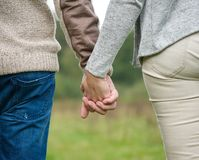 Male and female holding hands outdoors Stock Photos