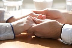 Male and female holding hands over table Stock Photo