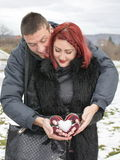 Male and female holding a snow shaped heart. Happy couple holding a snow shaped heart outdoors stock photo