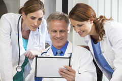 Male Female Hospital Doctors Using Tablet Computer. Male & female medical doctors medical team using tablet computer in a hospital office Royalty Free Stock Image