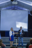 Male and Female Hosts on Stage In front of Group of People. Royalty Free Stock Images
