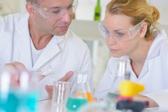 Male and female lab technicians conferring. Man Royalty Free Stock Photo