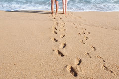 Male and female legs on beach near sea water Stock Image