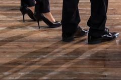 Male and female legs in black shoes and trousers on an old wooden parquet floor. Close-up. Royalty Free Stock Photos