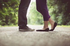 Male and female legs and black shoes, vintage tone Royalty Free Stock Image