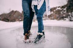 Male and female legs in boots stand in puddle with flying apart water splashes. Male and female legs in boots stand in puddle of melted water with flying apart Stock Photos