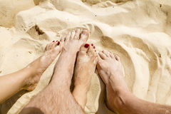 Male and female legs entwined in the sand on the beach Stock Photo