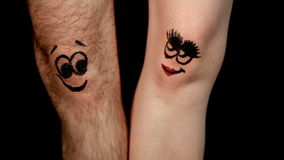 Male and female legs with funny faces falling in love Stock Photography