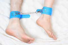 Male and female legs in handcuffs. couple in bed Stock Photo