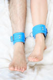 Male and female legs in handcuffs. couple in bed Stock Image