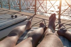 Male and female legs lie on a lounger on the pier at sunset stock image