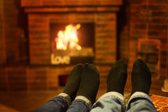 Male and female legs near the fireplace. Family concept Stock Photography