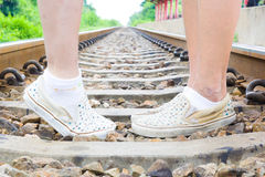 Male and female legs standing on rails train Royalty Free Stock Image
