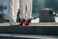 Male and female legs in white trousers. White and red shoes in the summer evening making a romantic scene of a date and love Royalty Free Stock Image