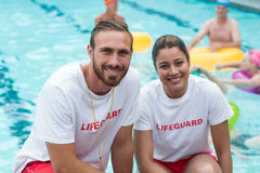 Male and female lifeguards crouching at poolside. Portrait of male and female lifeguards crouching at poolside Stock Photography
