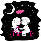 Male and female lovers kissing on a bench at night Stock Photo