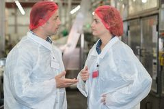 Male and female manual workers chatting stock photography