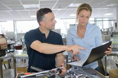 Male and female manual workers examining checklist royalty free stock image