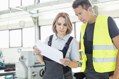 Male and female manual workers examining paper in industry stock image