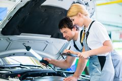 Mechanic team working in car workshop Royalty Free Stock Images