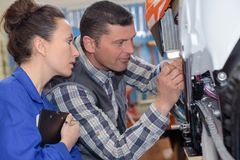 Male and female mechanic working on motorbike. Male Royalty Free Stock Photos
