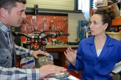 Male and female mechanics in discussion over seat motorcycle Royalty Free Stock Photography