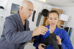 Male and female mechanics working on car piece Royalty Free Stock Images