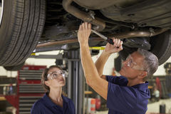 Male And Female Mechanics Working Underneath Car Together Royalty Free Stock Photos