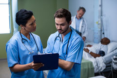 Male and female nurse having discussion over clipboard in ward. Male and female nurse having discussion over clipboard during visit in ward Stock Images