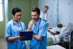 Male and female nurse having discussion over clipboard in ward. Male and female nurse having discussion over clipboard during visit in ward Royalty Free Stock Photo