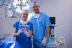 Male and female nurse using digital tablet in operation theater. At hospital Stock Photo