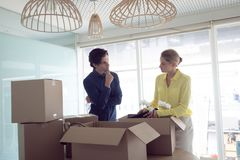 Male and female office executives interacting with each other. Front view of Caucasian male and female office executives opening boxes while interacting with royalty free stock image