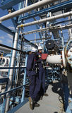 Male and female oil-workers. Two oil-workers inside large chemical oil and gas refinery Stock Photos