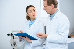 male and female ophthalmologists writing diagnosis stock photography