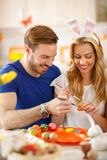 Male and female painting eggs for Easter stock photography