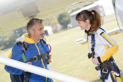Male and female parachutists under wing aircraft. Male and female parachutists under wing of aircraft Stock Photos