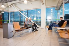 Passengers Waiting For Flight At Airport Terminal. Male and female passengers waiting for flight at airport terminal Stock Photos