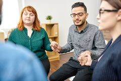 Participants of Group Therapy Session. Male and female patients with closed eyes sitting in circle and holding hands while participating in group therapy session royalty free stock image