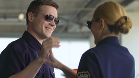 Male and female patrol officers giving high-five and going to squad car, team. Stock footage stock footage