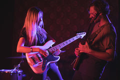 Male and female playing guitars in nightclub. Confident male and female playing guitars in nightclub Royalty Free Stock Photography