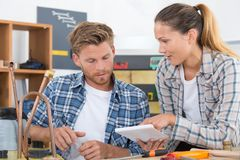 Male and female plumbers reviewing their tasks. Female Royalty Free Stock Images